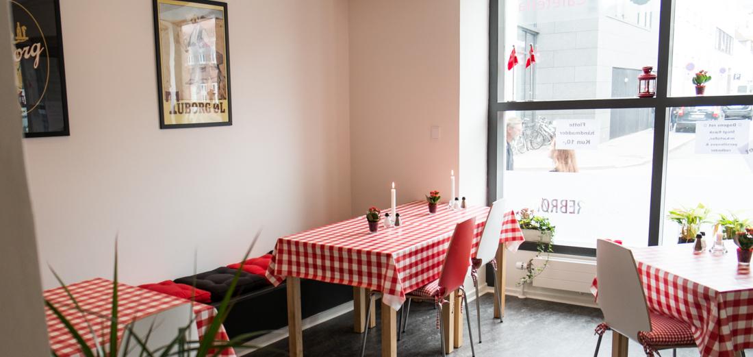 Borde med røde voksduge på Munkholts Cafeteria
