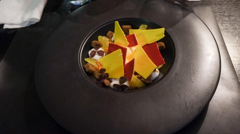 Iscreme, syltet abrikos, friske appelsinfileter, fransk honningkage og hvid chokolade farvet i forskellige farver på CANblau i Aarhus